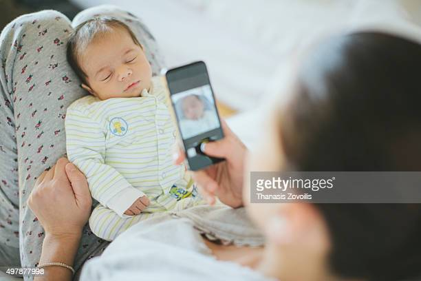 Mother taking photo of her newborn son