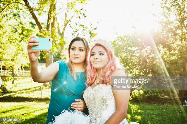 Mother taking selfie with daughter dressed in quinceanera gown in backyard