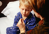 Mother taking sons (3-4) temperature in bedroom, close-up