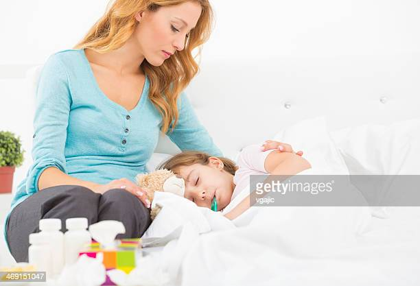 Mother Taking Temperature To Her Sick Child.