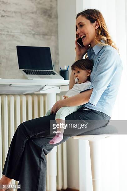 Mère parler au téléphone et tenant son bébé