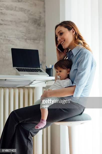 Madre parlando al telefono e con il Suo neonato