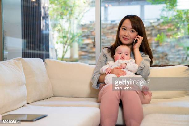 Mother talking on the phone whilst holding her baby