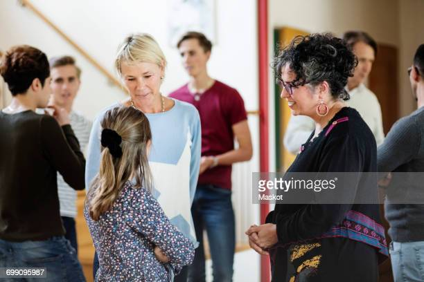 Mother talking to daughter against friends and family standing in living room
