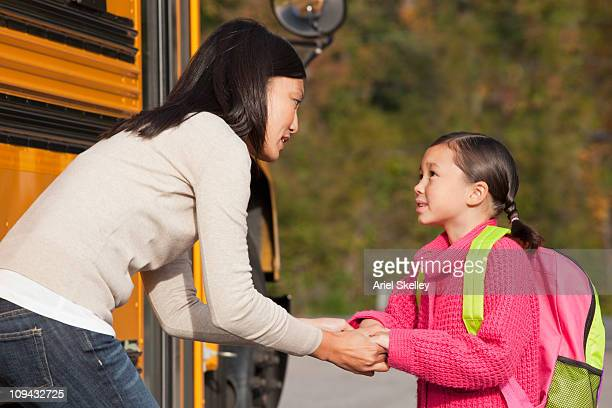 Mother talking to daughter as she gets on the school bus
