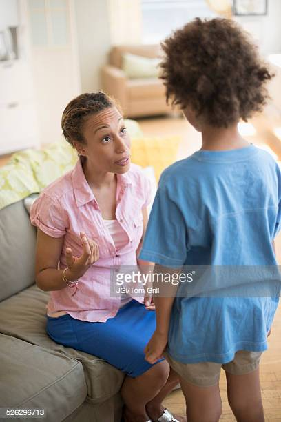 Mother talking to son in living room
