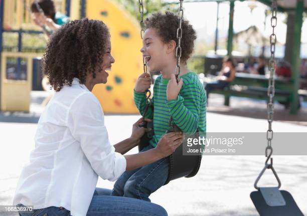 Mother talking to son on swing at park