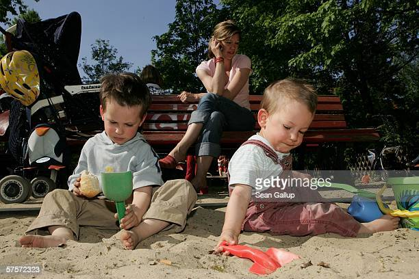 Annette Wassermann talks on a mobile phone while overseeing her sons Damian and Leander 16 months at a playground after work May 9 2006 in Berlin...