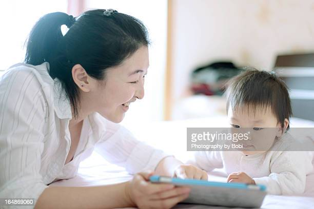 Mother teach daughter learn to use tablet