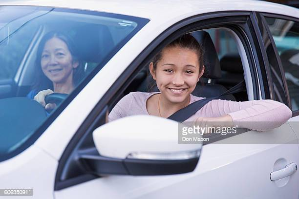 Mother teaching daughter to drive car