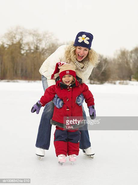 Mother teaching daughter (3-5) to skate on frozen lake, smiling