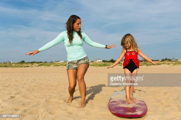 Mother teaching daughter to surf at beach