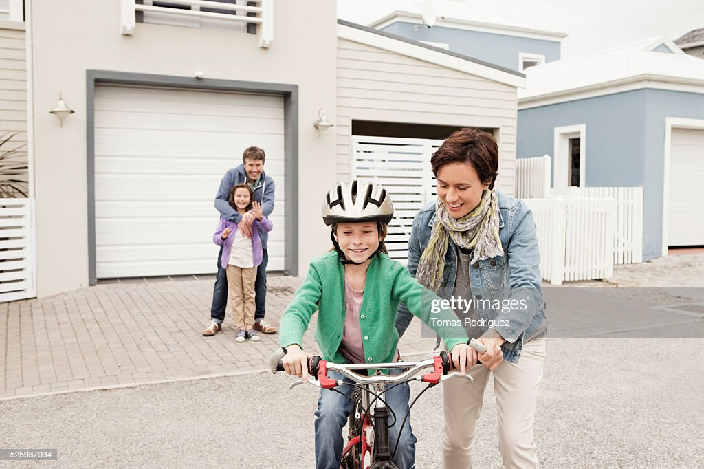 Mother teaching girl (8-9) riding bicycle : Stockfoto
