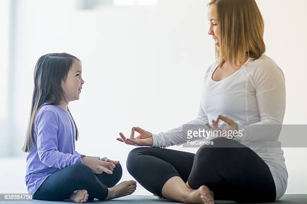 Mother Teaching Her Daughter to Meditate