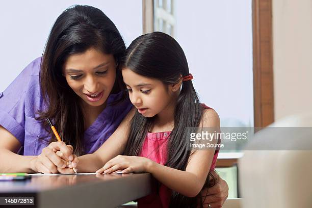 Mother teaching her daughter to write