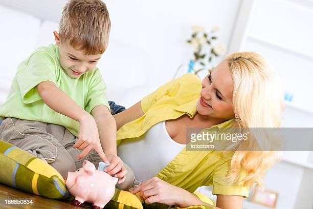 Mutter zeigt Ihr kleines Kind, um Geld zu sparen