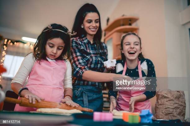Mother Teaching her Two Daughters How To Bake in Kitchen