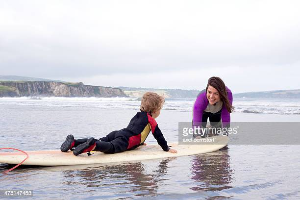 Mother teaching son how to surf