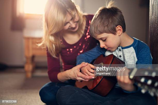 Mother teching son to play guitar