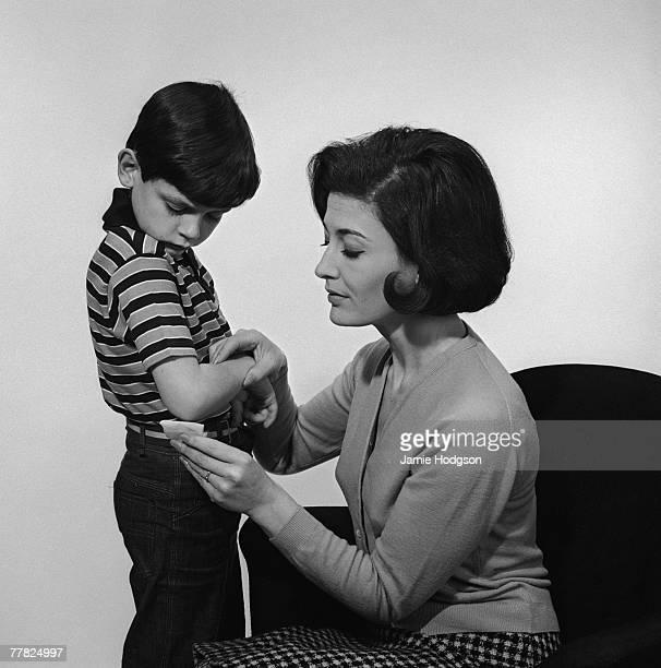 A mother tending her son's grazed elbow circa 1960