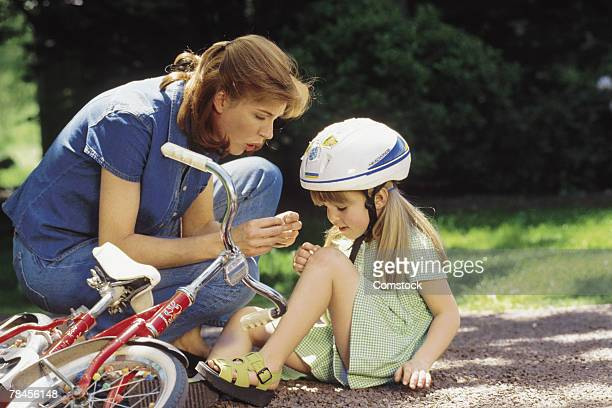 Mother tending to daughter who fell off bike