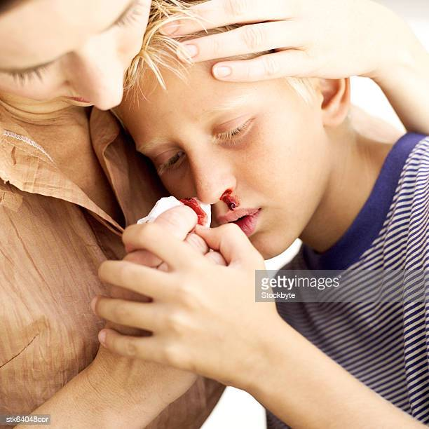 mother tending to her son's nosebleed