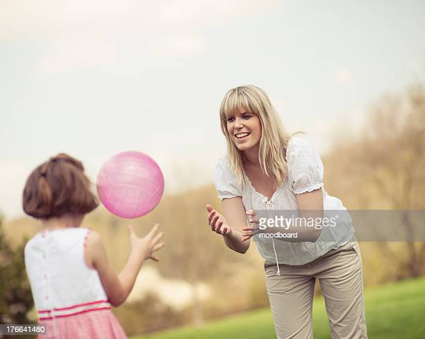 Mother throwing ball to daughter in park