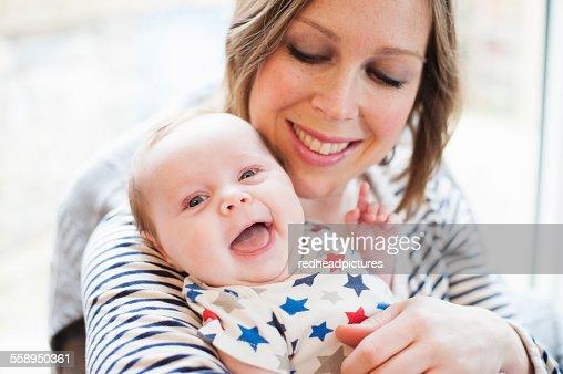 Mother tickling baby daughter