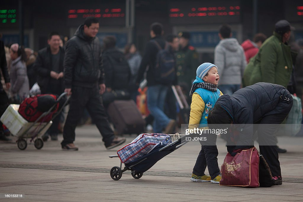 A mother ties her child's shoelaces as they arrive a Beijing Railway Station in Beijing on January 27, 2013