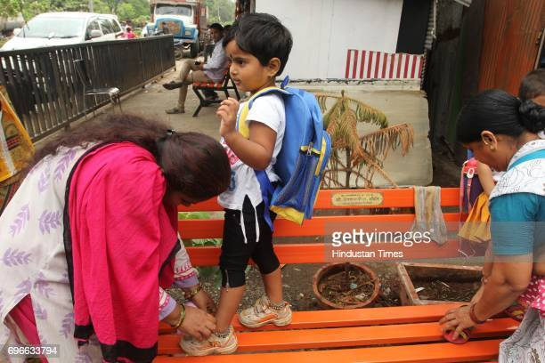 A mother ties shoe lace of her daughter as she goes for the first day of her school after a summer vacation at Thane on June 15 2017 in Mumbai India...