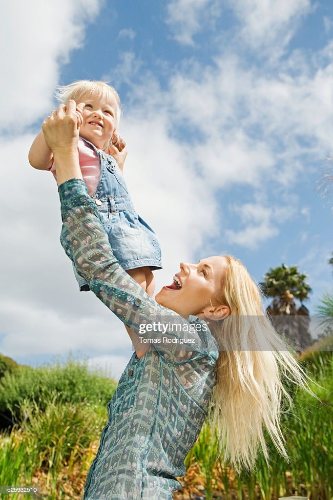 Mother tossing daughter (12-23 months) in air : Stock Photo
