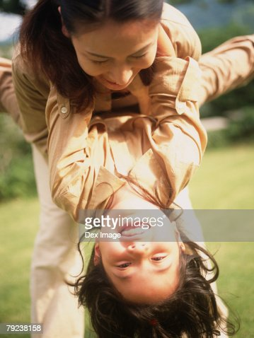 Mother tossing young daughter, close-up : Stock Photo