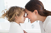 Mother touching nose with little girl wrapped in towel at bathroom