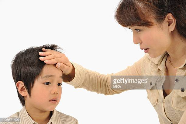 Mother touching son's forehead