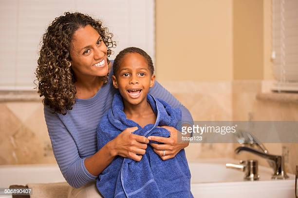 Mother towel dries son after his bath. Home bathroom.