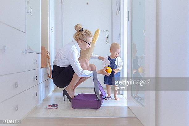 Mother trying to cheer her baby by giving her orange