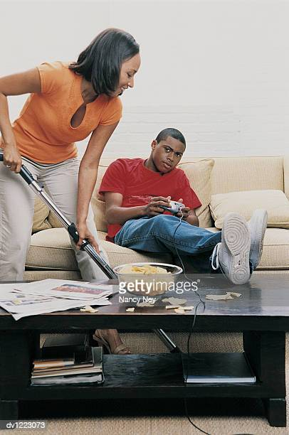 Mother Trying To Clean With a Vacuum Cleaner and Her Son Sitting on a Sofa Playing a Computer Game