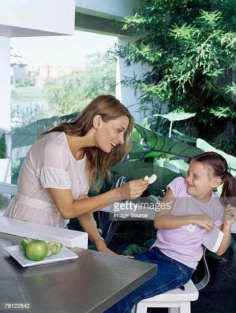 Mother trying to feed apple to daughter