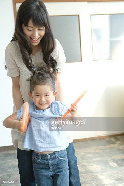Mother trying to hold daughter, smiling
