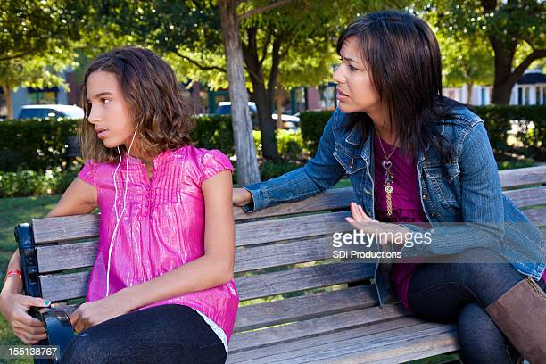 Mother trying to talk with teenager, who is ignoring her