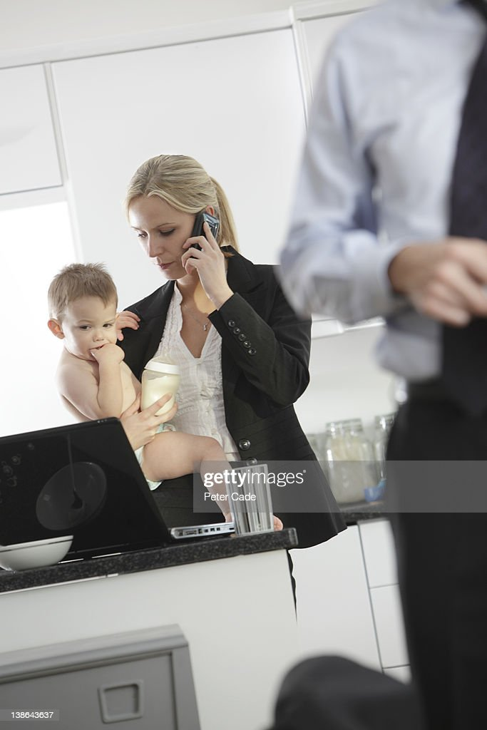Mother trying to work while holding baby : Stock Photo