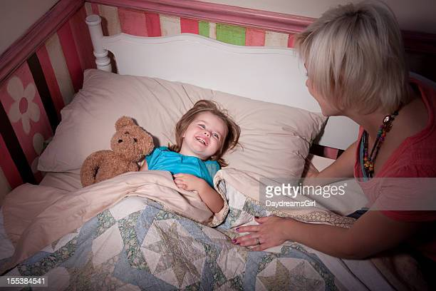 Mother Tucking Child in Bed