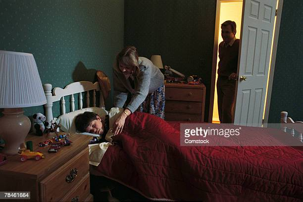 Mother tucking in son while father watches at door