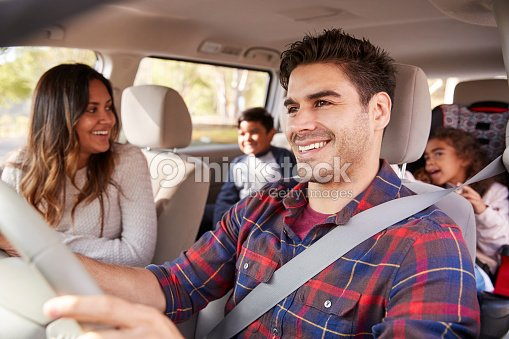Mother turns around to her children on the back seat of car : Stock Photo