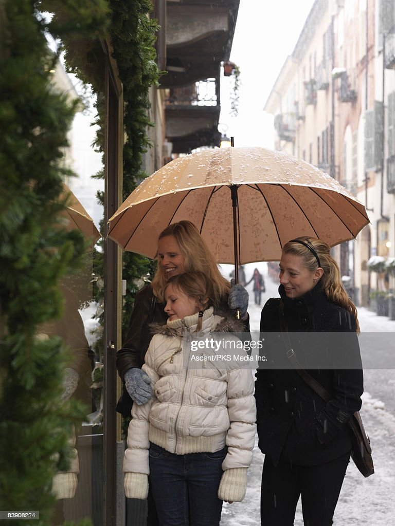 Mother & two daughters window shop in snow storm : Stock Photo