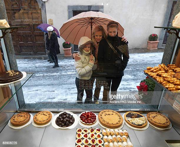 Mother & two daughters window shop in snow storm