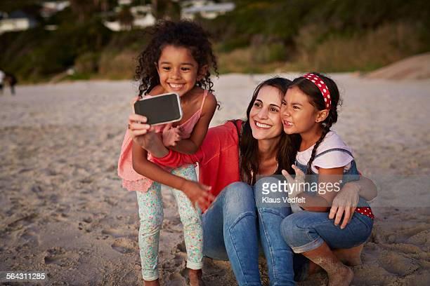 Mother & two kids making selfie on beach