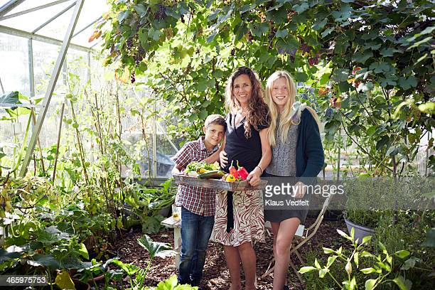 Mother & two kids standing in greenhouse