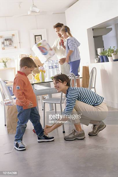 Mother tying boy's (5-7) shoes in kitchen, father and daughter (7-9)