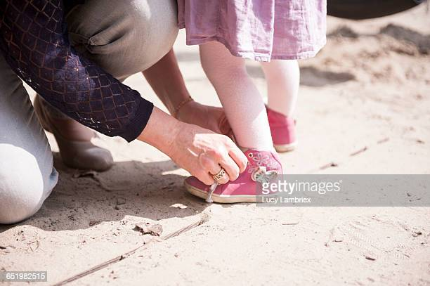 Mother tying her daughter's shoe laces